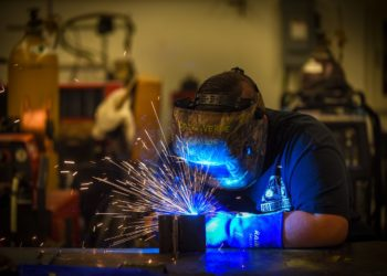 Person welding in blue light