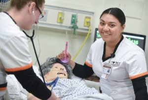 Students standing over nursing manikin