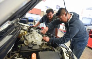 Two people working on car engine